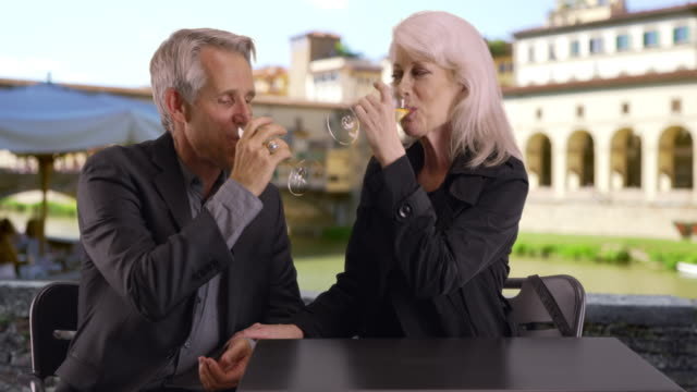 mature couple have a glass of wine by the ponte vecchio bridge - ponte点の映像素材/bロール