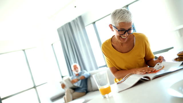 mature couple having a morning coffee at a kitchen counter. - magazine publication stock videos & royalty-free footage