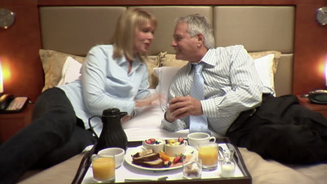 vídeos de stock e filmes b-roll de ms, mature couple having breakfast on hotel bed, montreal, quebec, canada - camisa e gravata