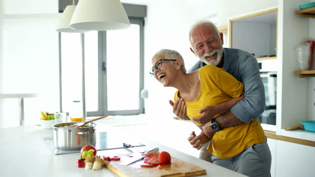 mature couple having fun while cooking lunch. - mature couple stock videos & royalty-free footage