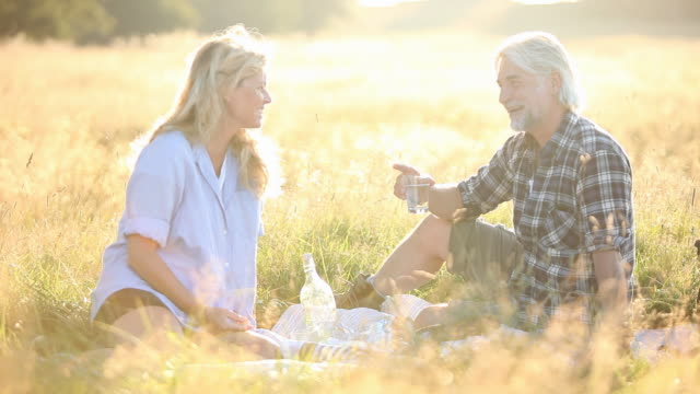 Mature couple having picnic in long grass in sunset