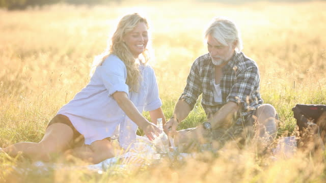 Mature couple having picnic in long grass