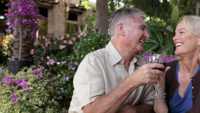 vídeos de stock, filmes e b-roll de mature couple having red wine, toasting to the camera - adulto maduro