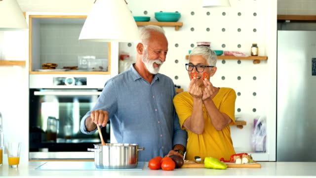 mature couple having while cooking lunch. - stove stock videos & royalty-free footage