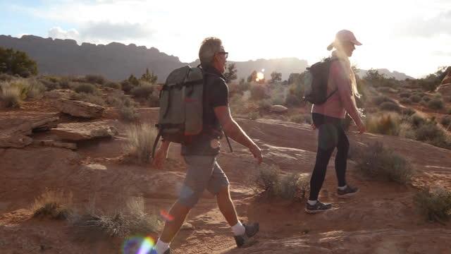 mature couple hike along faint desert pathway - moab utah stock videos & royalty-free footage