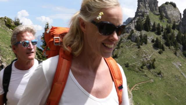mature couple hike along mountain ridge crest - hobbies stock videos & royalty-free footage