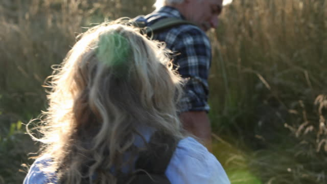 stockvideo's en b-roll-footage met mature couple hiking up hill in long grass - exploratie