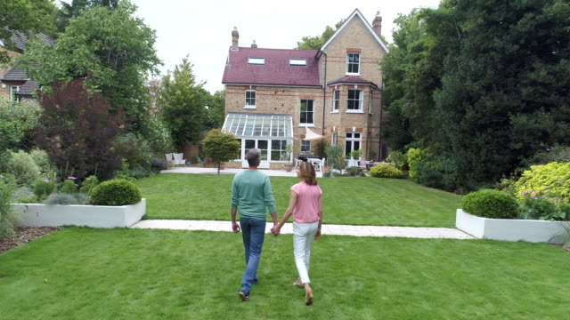 Mature couple holding hands and walking through garden towards back of house