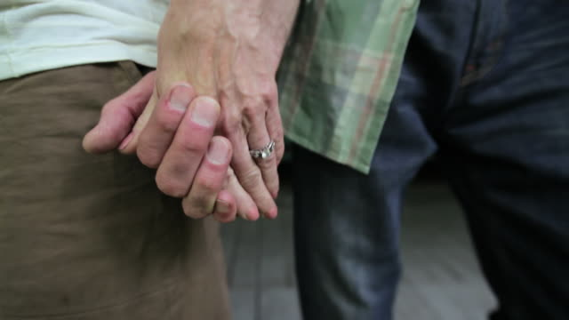 Mature couple holding hands, close-up