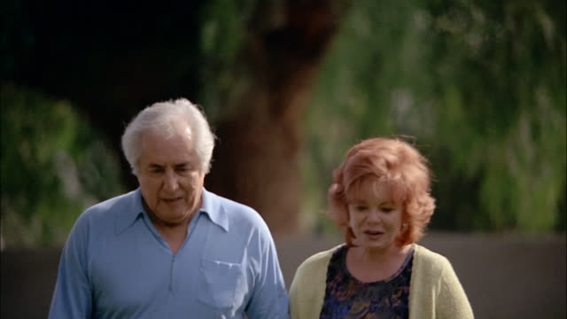 A mature couple holds hands as they walk.