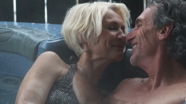 mature couple in a hot tub drinking wine and kissing - hot tub stock videos and b-roll footage
