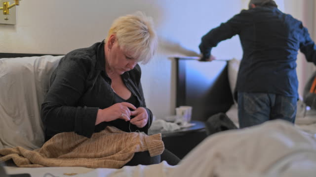 mature couple in a motel room. caucasian-white body-positive attractive woman fixing a sweater, sitting on a bed; man packing stuff in the backdrop. - body positive stock videos and b-roll footage