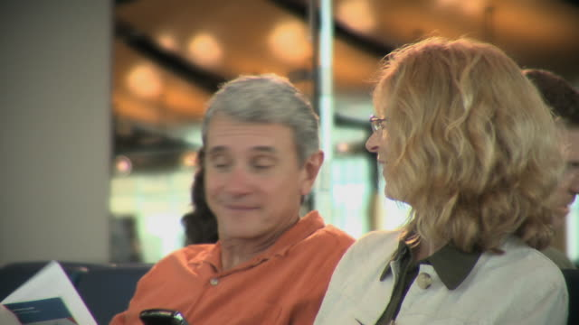 CU Mature couple in airport lounge, woman showing phone to man, Appleton, Wisconsin, USA