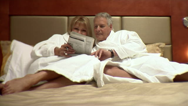 ms, mature couple in bathrobes doing crossword puzzle on hotel bed, montreal, quebec, canada - crossword stock videos and b-roll footage