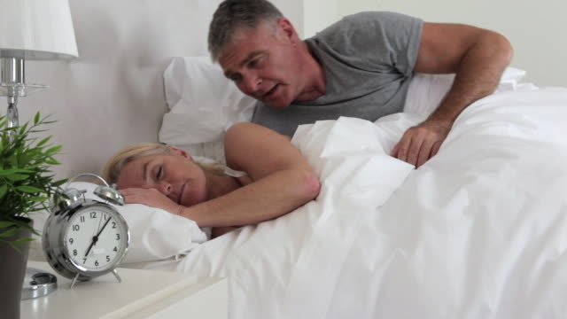 mature couple in bed, man wakes wife with a kiss - duvet stock videos & royalty-free footage