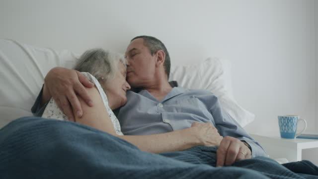 vídeos de stock e filmes b-roll de mature couple in bed together. man kissing forehead of his wife. - casal de meia idade