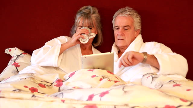 Mature couple in bedroom looking at computer tablet
