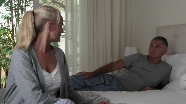 mature couple in bedroom - zurücklehnen stock-videos und b-roll-filmmaterial