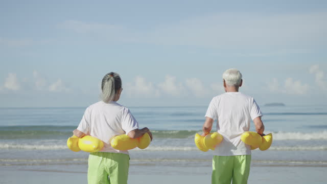 mature couple in couple cloth, white t-shirt, green shorts at the beach, senior adult with yellow swimming ring running to sea with happiness in holiday summer. - swimming shorts stock videos & royalty-free footage