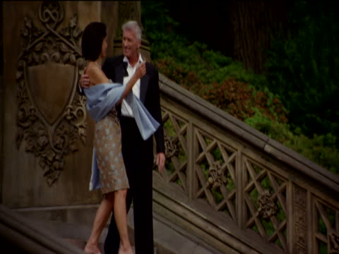 mature couple in evening dress kiss and walk side by side down ornate stone steps in central park, new york - evening gown stock videos and b-roll footage