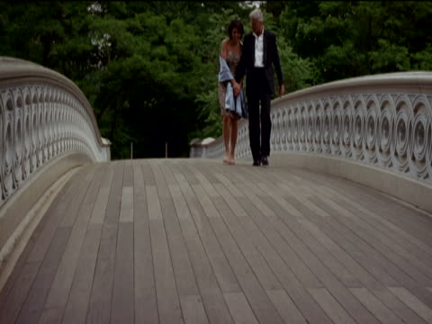 mature couple in evening dress walk side by side over a stone bridge, man twirls the woman around, central park, new york - mature couple stock videos & royalty-free footage