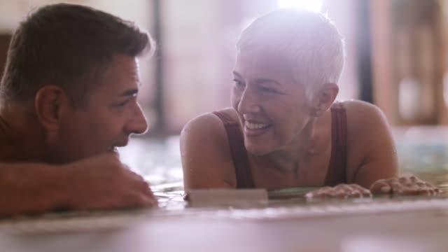vidéos et rushes de couple d'âge mûr dans un bain à remous - établissement de cure