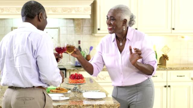 Älteres Paar in Küche, serviert Kuchen, Wein trinken