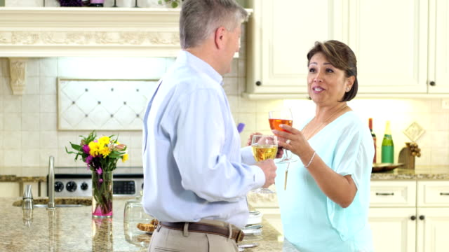 Mature couple in kitchen, serving cake, drinking wine