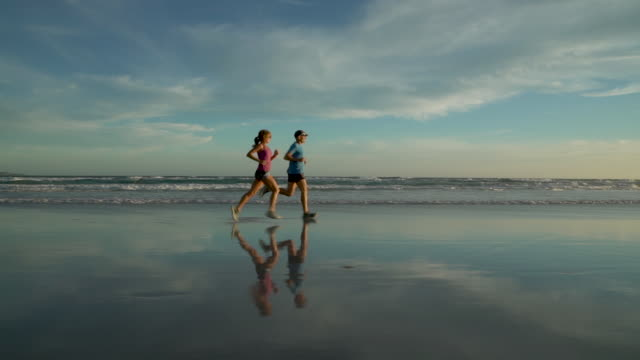 vídeos y material grabado en eventos de stock de mature couple jogging on a beach at sunset - toma en travelling