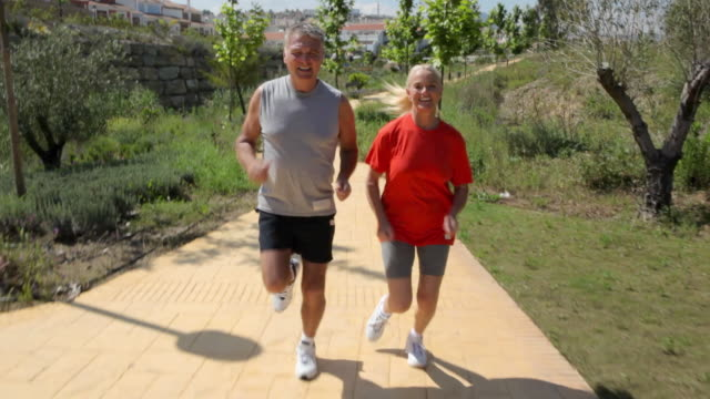 vídeos y material grabado en eventos de stock de mature couple jogging on path, rear point of view - 55 59 años