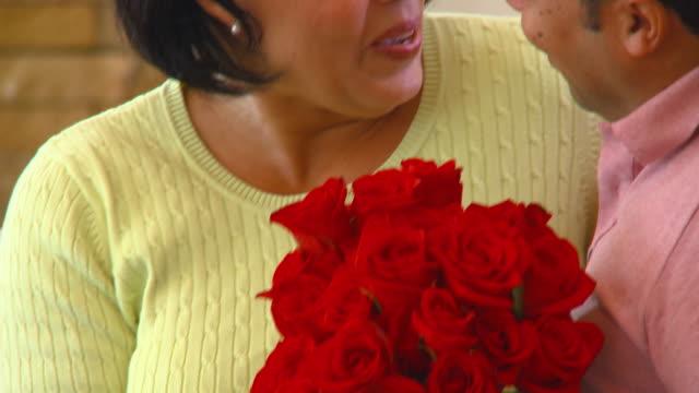 stockvideo's en b-roll-footage met cu, tu, focusing, mature couple kissing, man giving red roses to woman, richmond, virginia, usa - eskimokus geven
