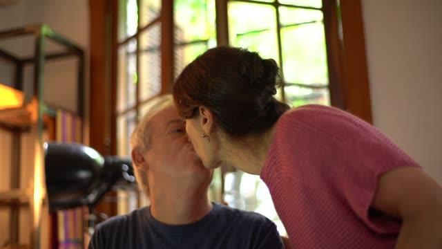 vídeos de stock, filmes e b-roll de maduras casal a beijar em home office - casal de meia idade