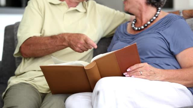 vídeos de stock, filmes e b-roll de mature couple laughing while looking at a book  - cor de cabelo