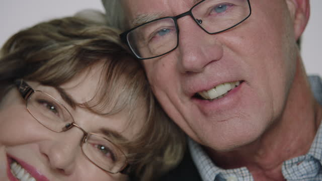 cu slo mo. mature couple lean together and smile into camera in studio. - french manicure stock videos and b-roll footage
