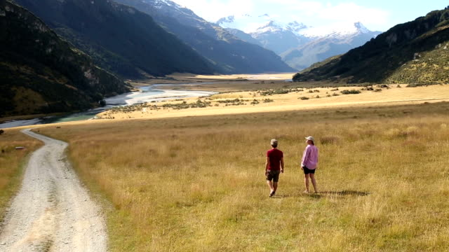 mature couple leave 4x4 to walk through field towards mountain view - getting out stock videos and b-roll footage