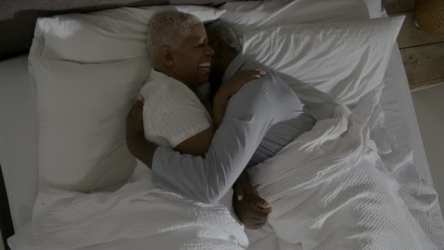 a mature couple lie in bed together - mature couple stock videos & royalty-free footage