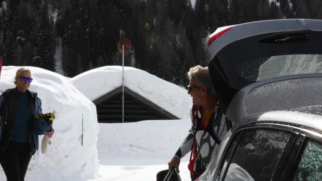 vídeos y material grabado en eventos de stock de mature couple load ski equipment into car - abrigo de invierno
