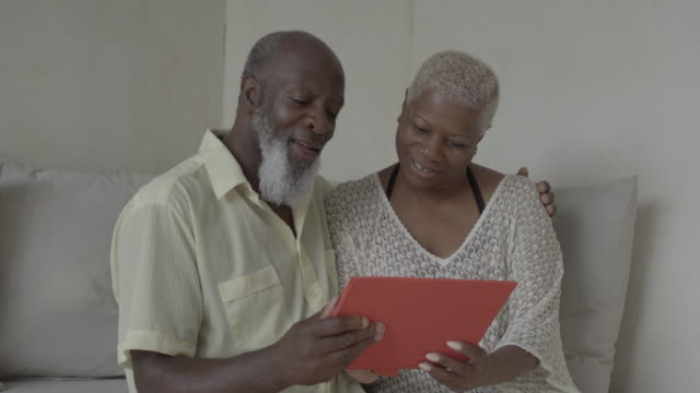 mature couple look at digital tablet (medium close) - enjoyment stock videos & royalty-free footage