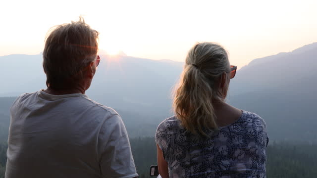 mature couple look off to distant mountains and forest, from promontory - hand on chin stock videos & royalty-free footage