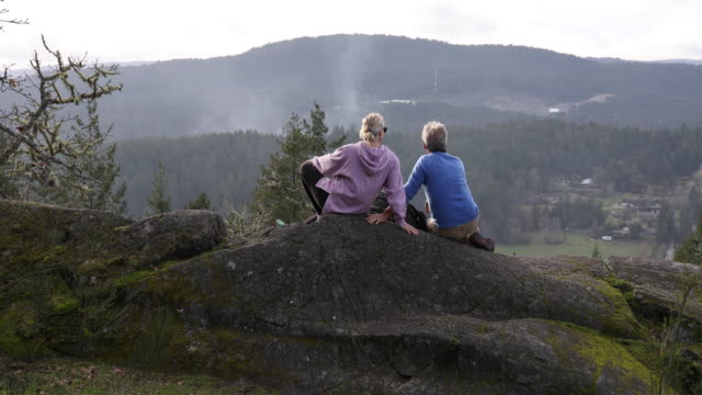 mature couple look off to vista from rock knoll - 60 64 years stock videos & royalty-free footage