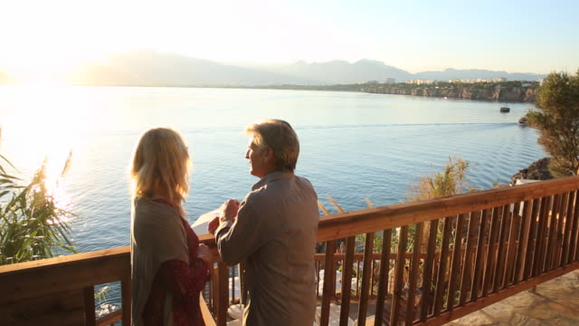 vídeos de stock e filmes b-roll de mature couple look out across sea from deck railing - sargaço