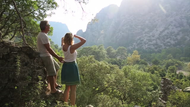 mature couple look out from forest canopy to mountains, sunrise - copertura di alberi video stock e b–roll