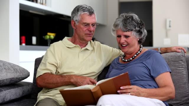 vídeos de stock, filmes e b-roll de mature couple looking at a book together - cor de cabelo