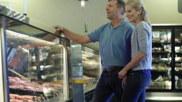 mature couple looking at display case in a butcher shop - präsentation hinter glas stock-videos und b-roll-filmmaterial