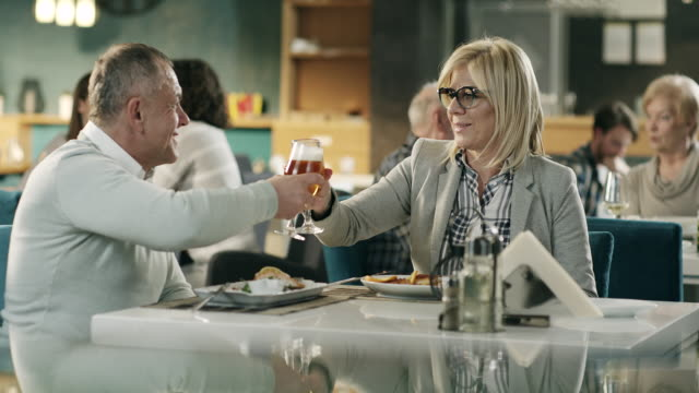vídeos de stock e filmes b-roll de mature couple looking at each other and holding glasses with beer in restaurant - casal de meia idade