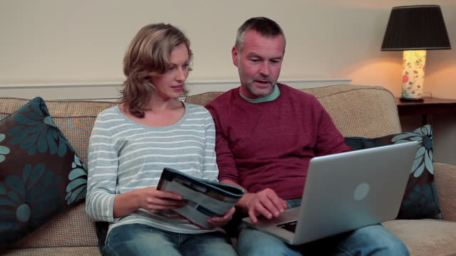 Mature couple looking at magazine and using laptop
