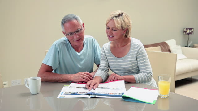 Mature couple looking at magazine