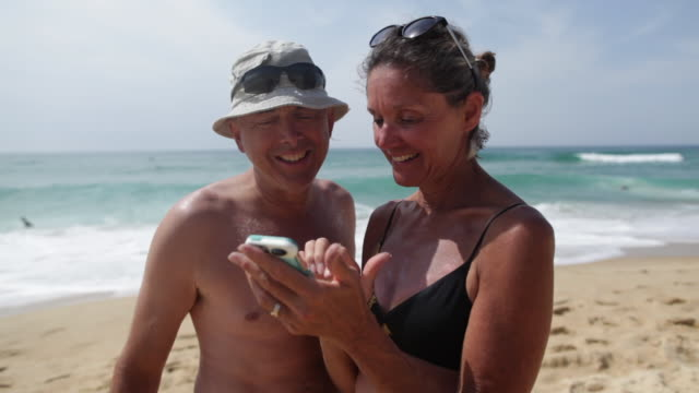 Mature couple looking at photographs on cell phone, laughing at the beach in the South of France.