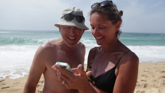 Mature couple looking at photos on cell phone, laughing, talking at the beach in the South of France.