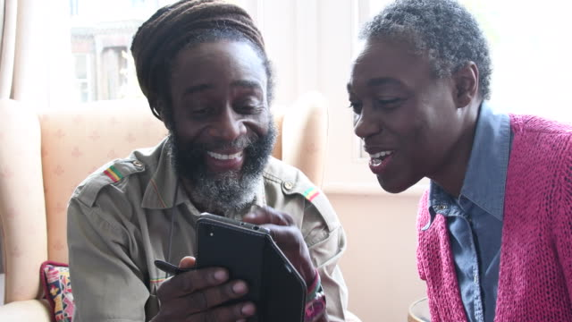 Mature couple looking at smartphone together and laughing